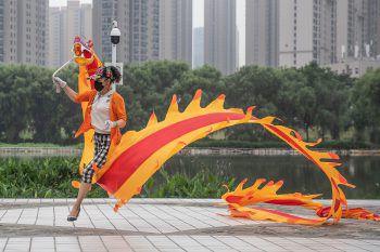 <p>               Wuhan.             </p><p>Akrobatisch: Diese Dame beweist trotz Maske viel Geschick beim rhythmischen Tanz mit ihrem Drachen.</p>