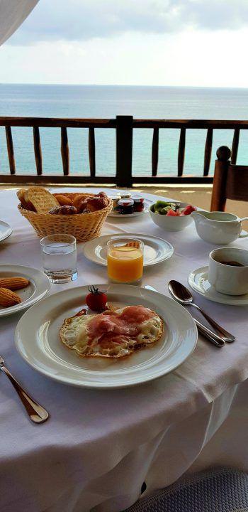 """<p class=""""caption"""">Am nächsten Morgen erwartet uns auf der Panorama-Terrasse des Club-Hotels ein wunderschön angerichtetes Frühstück mit Meerblick. Maitre Giulio erklärt, dass in dieser Saison die Gäste am Vortag Ihr Frühstück aus einer reichhaltigen Auswahl bestellen und es dann am nächsten Morgen prompt am Tisch serviert bekommen. Abends, erklärt uns Giulio, stehen drei Menüs zur Auswahl, jeweils vier Gänge.</p><p class=""""caption"""" />"""