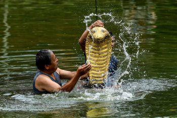 """<p>Bhaktapur. Traditionell: Zwei Männer zollen der Hindu-Schlangen-Gottheit """"Nag"""" Respekt.</p>"""