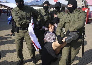 Maskierte Polizisten führen eine Demonstrantin ab.Foto: AP