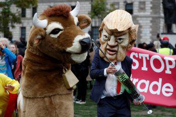 London. Satire: Eine Demonstrant mit Donald Trump-Maske hält bei einer Demo zur anstehenden US-Präsidenten-Wahl eine riesige Spritze in Richtung eines anderen Teilnehmers im Kuh-Kostüm. Fotos: AFP (4),, Reuters