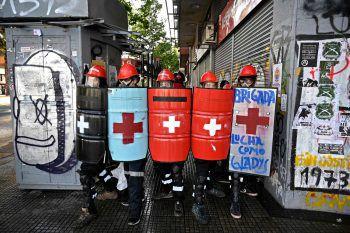 """<p>Santiago. """"Wasser marsch"""": Medizinische Ersthelfer schützen sich bei Protesten gegen den chilenischen Präsidenten Sebastian Pinera mit Schildern vor Wasserwerfern.</p>"""