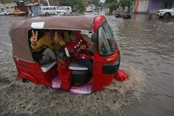 <p>Baghdad. Land unter: Ein Tuk-Tuk fährt nach heftigen Regenfällen durch die überfluteten Straßen der irakischen Metropole.</p>