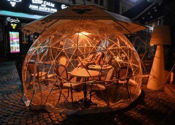 <p>Bukarest. Corona-Maßnahmen: In diesem Schutz-Zelt vor einer Bar ist ein Gast am Tisch eingeschlafen.</p>