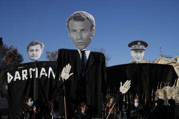 <p>Paris. Spott: Demonstranten tragen eine riesige Plakat-Figur des französischen Präsidenten Emmanuel Macron mit sich.</p>