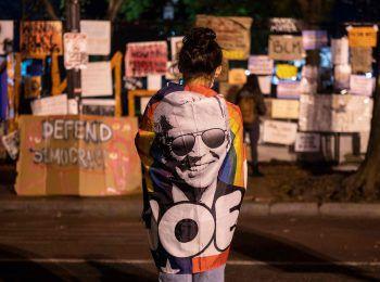 """<p>Washington. Wahl: Eine Frau wartet in der Nähe des Weißen Hauses auf die Ergebnisse der Präsidentenwahl, eingehüllt in eine Flagge mit der Abbildung des demokratischen Kandidaten Joe Biden. Ihr gegenüber protestieren Aktivisten der """"Black Lives Matter""""-Bewegung.</p>"""