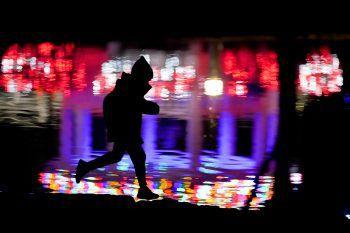 Kansas. Festlich: Ein Junge spielt und rennt an einem Teich entlang. Die Weihnachtsbeleuchtung eines Nachbarhauses spiegelt sich im Wasser.