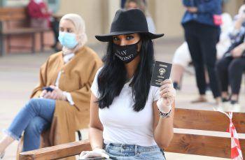 <p>Kuwait Stadt. Wahlen: Eine Frau mit Maske und Handschuhen wartet mit ihrem Pass darauf, ihre Stimme für die Parlamentschafts-Wahlen in Kuwait abgeben zu können.</p>