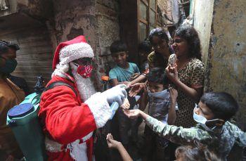 <p>Mumbai. Hilfe: Ein Mann im Santa Claus-Kostüm desinfiziert in einem der größten Slums Asiens die Hände von Kindern.</p>
