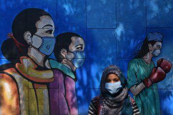 <p>Neu Delhi. Kunst: Eine Frau mit Mund-Nasenschutz vor einem Wandgemälde ganz im Zeichen der Covid-19-Pandemie. Fotos: AFP (2), APA, AP</p>