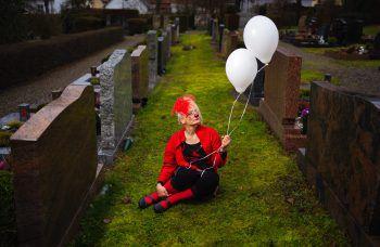 """Lichtenfels. Schräg: Die deutsche Psychologin Birgit Sauerschell alias (Klinik-)Clown Kalaa Knuffl sitzt als melancholischer """"Beerdigungs-Clown"""" mit Luftballons auf einem Friedhof in Bayern. Fotos: AFP, AP, APA, dpa"""