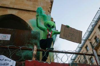 <p>Beirut. Schräg: Ein als Alien verkleideter Regierungsgegner steht auf einer mit Stacheldraht gesicherten Barriere. Fotos: AFP</p>