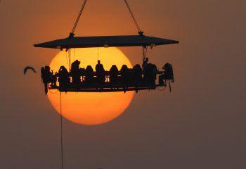 <p>Vereinigte Arabische Emirate. Cool: Menschen genießen ihr Abendessen in einem Sky Restaurant bei Sonnenuntergang in rund 50 Meter Höhe. Der Tisch ist an einem Kran befestigt.</p>