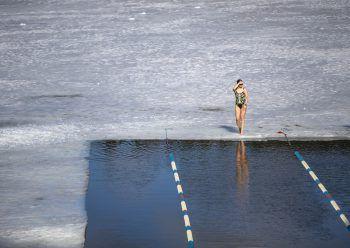 <p>Vilnius. Eiskalt: Eine Frau geht an den Start für einen Eisschwimm-Wettbewerb in Litauen. Die Teilnehmer müssen ein 25 Meter langes Eisloch durchschwimmen.</p>