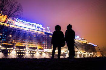 """Zwei Menschen blicken auf das Kreuzfahrtschiff """"Odyssey of the Seas"""".Foto: APA"""