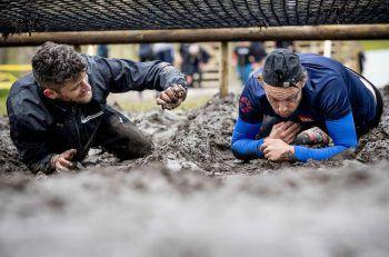 """<p>Amsterdam. Matschig: Zwei Männer robben beim """"Mud Masters""""-Wettbewerb durch den Schlamm. Das Rennen ist trotz Lockdown in den Niederlanden erlaubt.</p>"""