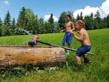 """<p class=""""caption"""">Raphael (9), Adrian (4) und Jonathan (2) kühlen sich bei den warmen Temperaturen in einem Brunnen in Alberschwende ab.</p>"""