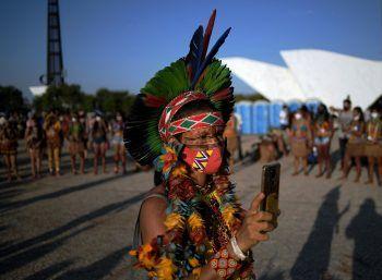 <p>Brasilia. Protest: Ein brasilianischer Ureinwohner in traditionellem Gewand schießt ein Foto während einer Demo gegen die indigenenfeindliche Politik Bolsonaros.</p>