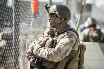 <p>Kabul. Bedrückend: Ein US-Marine hält inmitten des Chaos auf dem afghanischen Flughafen ein Kind in seinen Armen und versucht es, zu beruhigen.</p>