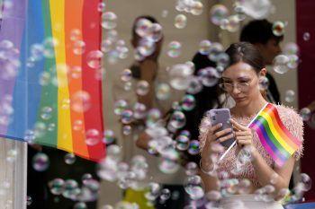 <p>Belgrad. Bunt: Eine Frau hält während der jährlichen Pride Parade eine Regenbogenflagge und ist umringt von Seifenblasen.</p>