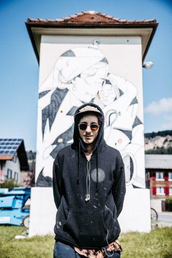 """<p class=""""title"""">               """"Migration, Klima und Liebe als Thematik""""             </p><p>David Leitner, Wandmaler/Künstler, Wien: """"Meine Arbeiten in Wolfurt haben einerseits Migration und Klimawandel zum Thema, andererseits Liebe und Geborgenheit. Beides Dinge, die die Menschen sehr stark bewegen. Ich wollte keine Ansichtskarte von Wolfurt malen. Das wäre zwar schön gewesen, hätte aber sicherlich nicht den selben ,Impact' gehabt.""""</p>"""