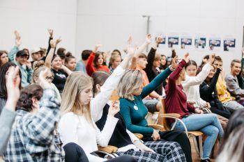 """<p class=""""caption"""">Dieses Bild zeigt die rege Teilnahme der Schüler und Schülerinnen an der Diskussion. Oder? Nein, Achtung: Fake News! Fotos werden gerne aus dem Zusammenhang gerissen, so auch hier. Tatsächlich geht es im Bild um die Abstimmung über das Mittagessen.</p>"""